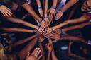ein Team legt die Hände übereinander im Kreis